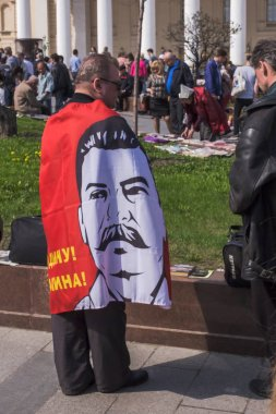 Moscow, Russia - May 1, 2018: Celebrating International Workers' Day at Teatralnaya Square.  A man wears a flag with a portrait of Stalin and an inscription