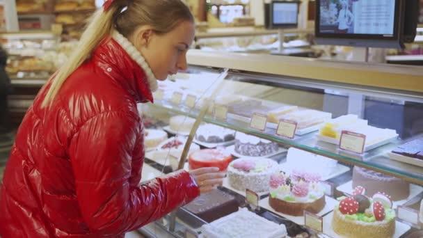 Nő vásárol néhány cookie-kat és süteményeket egy cukrászda - Gyönyörű lány előtt édes édességbolt ablak