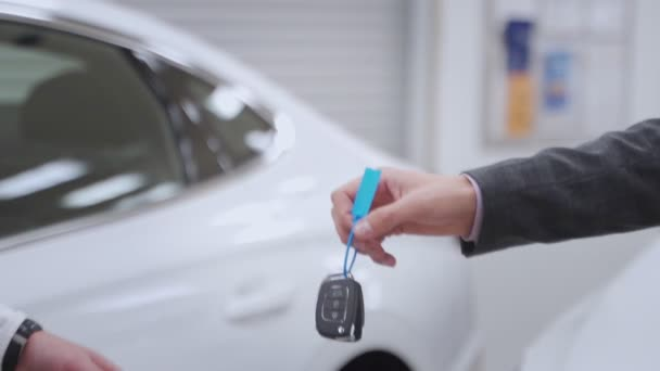Car dealer handing over new car key to customer at showroom