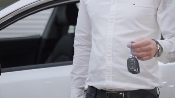 Attractive young man smiling happily holding car keys to his newly bought car