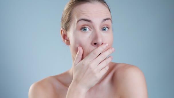 Meglepett nő, aki eltakarta a száját és a kamerába nézett.