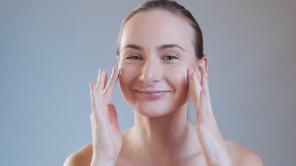 Žena si nanáší krém na obličej. Pronásledování krásy