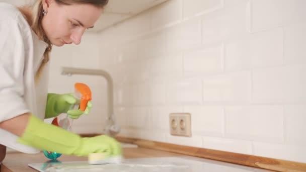 Frau reinigt Induktionsherd in Küche mit Sprühflasche und Schwamm