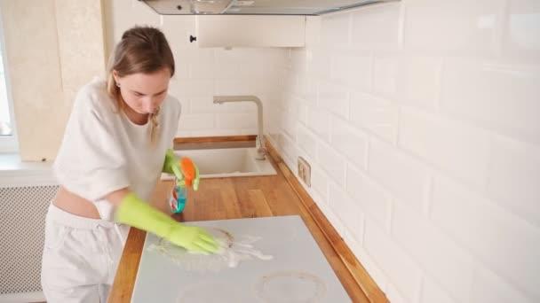 Ženské školník čištění sporák s sprejem láhev v kuchyni