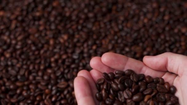 Kávová zrnka se zavírají. Ženské ruce drží kávu.