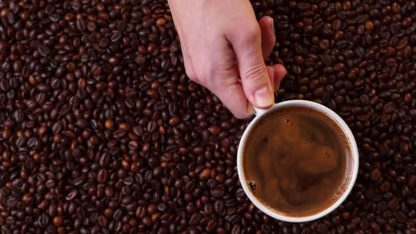 Horní pohled na ruku s šálkem černé kávy dát ji na kávová zrna pozadí.