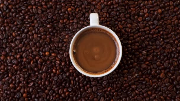 Top view of white cup of black coffe on coffee beans