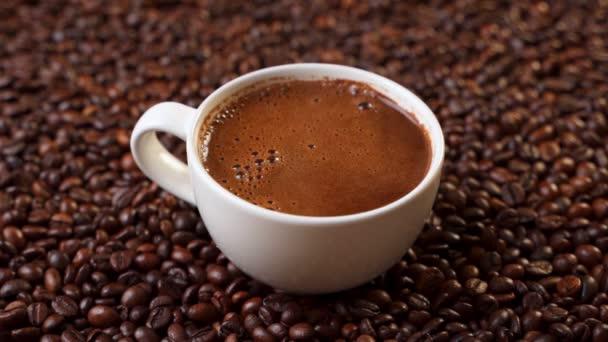 Boční pohled na bílý šálek černé kávy na kávových zrnech