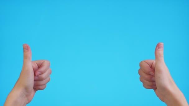 Frau zeigt mit den Händen auf Kopierraum und zeigt Daumen nach oben über blauem Hintergrund