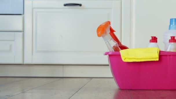 Různé láhve čisticích prostředků a čisticích prostředků, žínky v růžovém kbelíku v pokoji na podlaze
