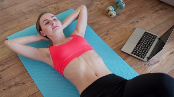 Sport, domácí trénink, on-line fitness kurzy. Mladá žena dělá tisknout na Mat doma při sledování video průvodce na notebooku