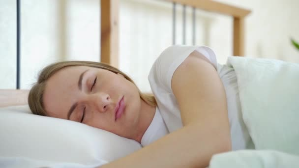 A nő teljesen kipihenten ébred az ágyában. Nő nyújtózkodik az ágyban, miután felébredt.