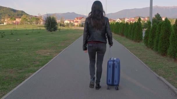 eine Frau in Lederjacke geht mit einem Koffer den Bürgersteig hinunter, im Hintergrund Berge.