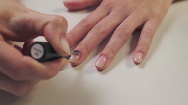 Žena si lakuje nehty. Žena dělá manikúru. Ta holka se stará o nehty. Detailní záběr. Zpomalení.