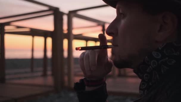 Nahaufnahme, ein Mann mit Hut und Lederjacke, der bei Sonnenuntergang eine Zigarre raucht. 50 fps