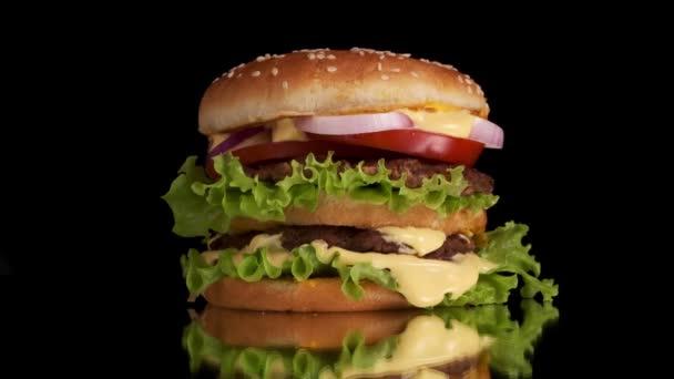 Velký, lahodný hamburger s hovězím masem Patty, salátem a zeleninou, pozadí je v plamenech. Zpomal. Plameny v pozadí.