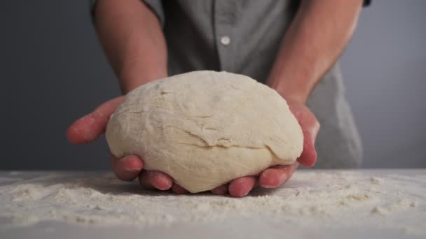 A male baker in a shirt shows the dough, then knead it. Close-up.