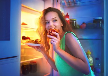girl taking food from refrigerator at night