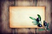 Fotografia Ramo di oliva fresco sopra priorità bassa di carta