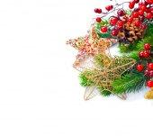 Stelle decorative di Natale con i rami di abete su priorità bassa bianca