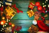 Fotografie Vánoční dárky, svíčky, spořádáme a perník na zelený dřevěný stůl