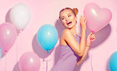 joyful teenage girl with colorful air balloons having fun over pink background