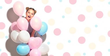joyful teenage girl with colorful air balloons having fun over white background with dots