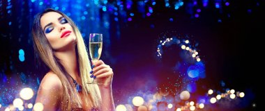 model girl drinking champagne over holiday glowing background