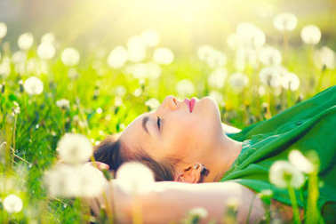 Young woman lying on field in grass