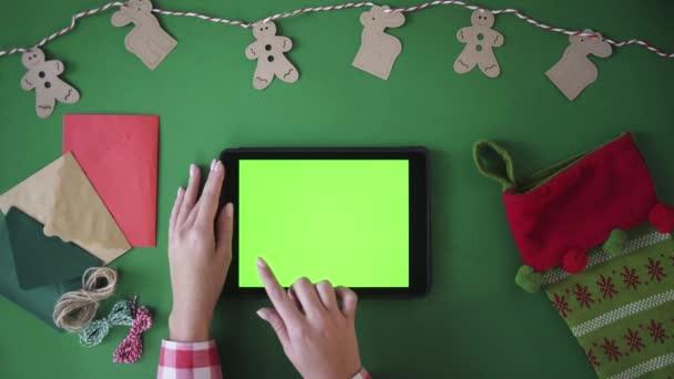 Žena prst švihnout obrazy vlevo a vpravo klepnutím na zelené obrazovce zařízení tablet. Vánoční koncepce s sváteční dekorace na pozadí zeleného stolu. Pohled shora. Chroma klíč