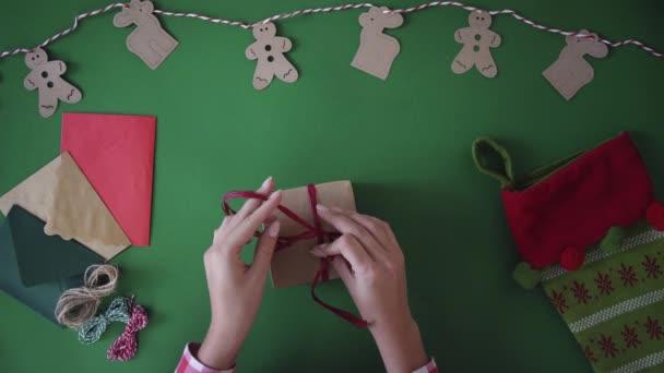 Nő csomagolás cristmas jelen, ajándék, a zöld asztalnál háttér szünet feldíszítés. A fenti felülnézet.
