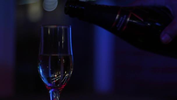 Pohled opilý muž na sklenici na víno, ve kterém se nalije šampaňské.