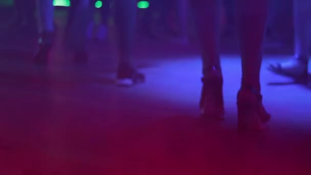 Beautiful female feet in shoes on heels move to music in a nightclub.