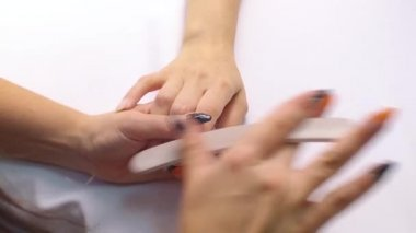 Slow Mo. The manicure master adjusts the shape of the nail with a hand polishing tool.
