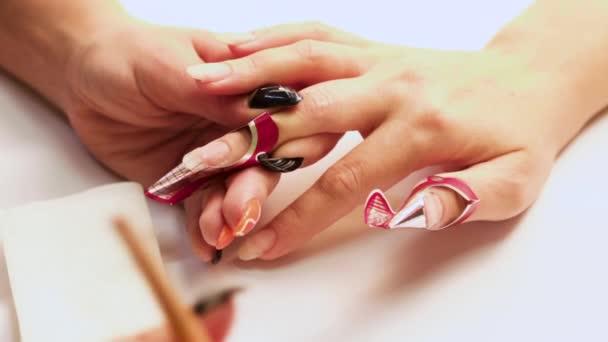 Hlavním manikúra platí štětcem gel a tvoří nehty na prstech pravé ženské ruky. Detail.