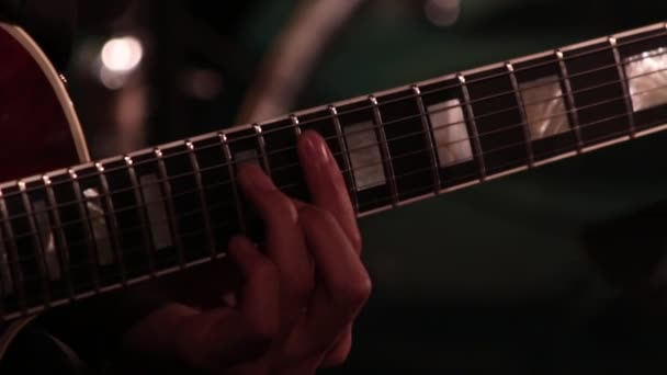 A male hand while playing an electric guitar. Close-up. Footage on a musical theme.