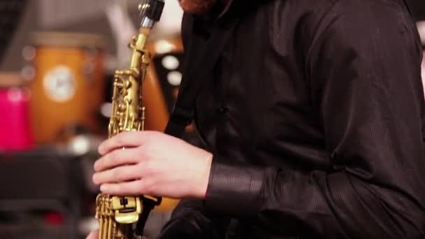 Egy ember, egy fekete póló szakáll érzelmileg játszik a szoprán szaxofon. Közeli kép:.