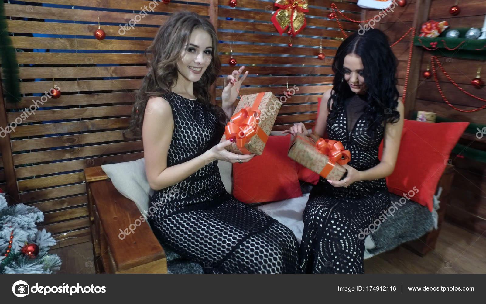 1a79fc809384 Δύο όμορφα κορίτσια σε μαύρα φορέματα με γιορτινά κουτιά στα χέρια τους–  εικόνα αρχείου