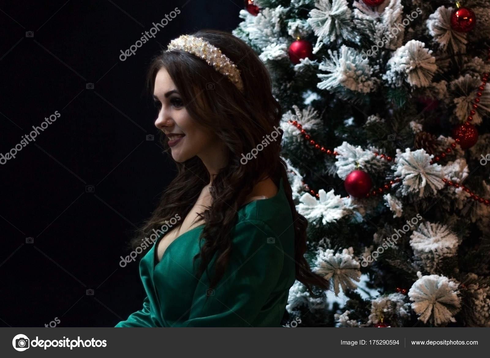 Schöne Mädchen in ein grünes Kleid in der Nähe von Neujahr Baum auf ...