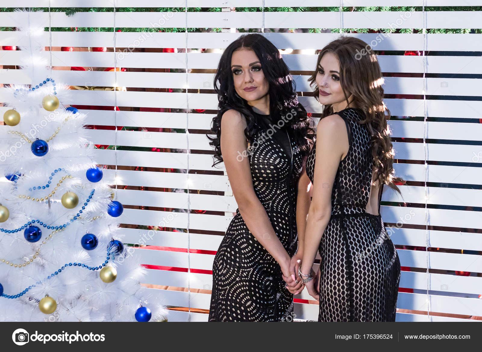 6658dda911f1 Δύο όμορφες νεαρές γυναίκες σε μαύρο βραδινά φορέματα μόνιμη κοντά ...