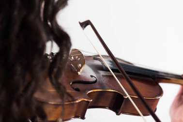 Girl playing the violin. Close-up. View from the shoulder side through the hair. The bow touches the strings. Musical theme. White background.