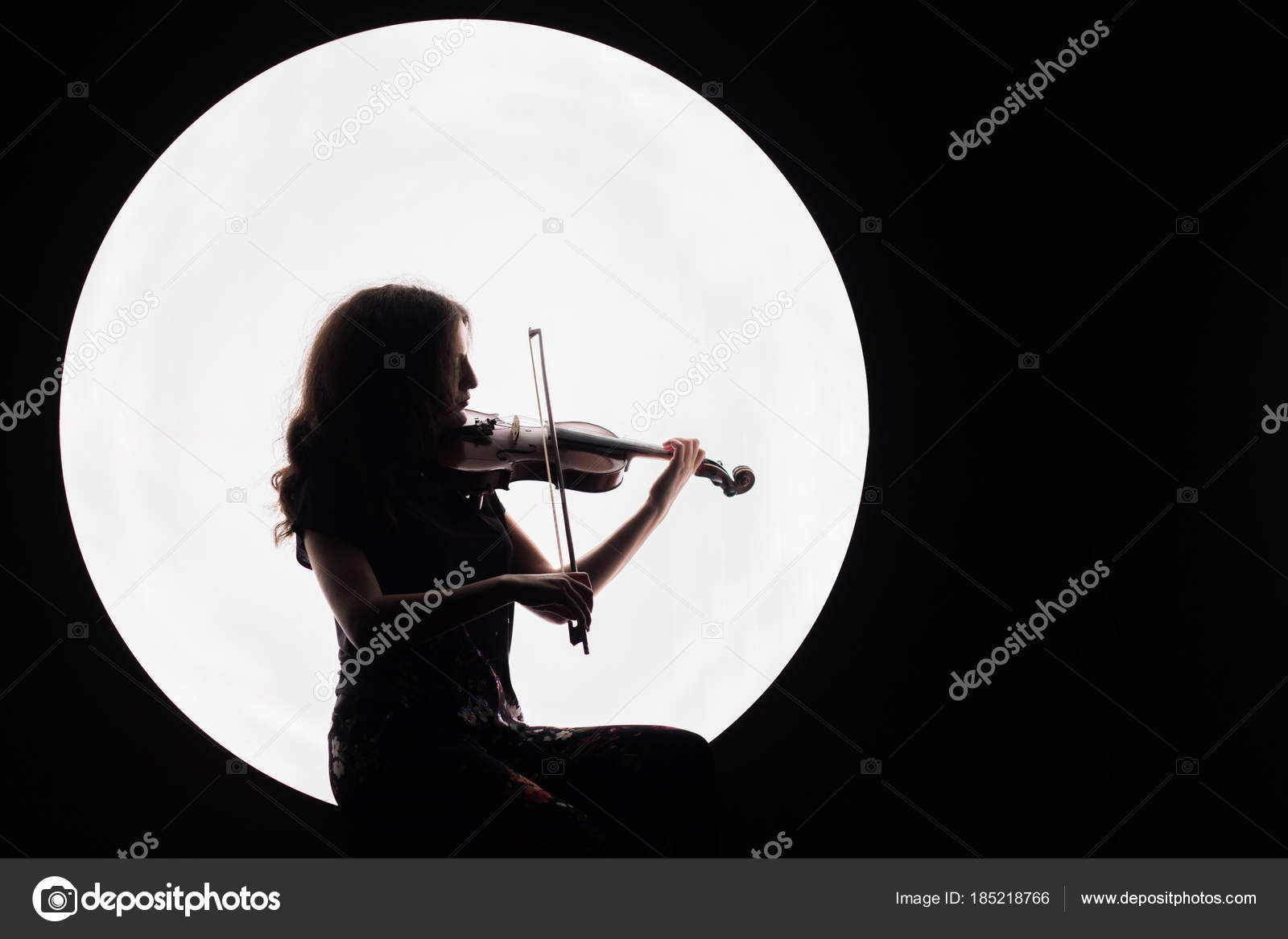 Silhouette of a beautiful brunette girl playing the violin  Concept
