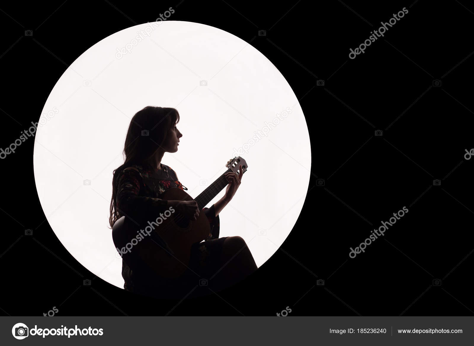 Silhouette of a beautiful brunette girl playing guitar