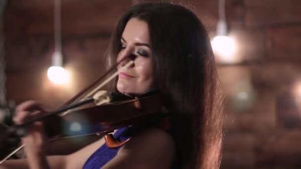 Krásná brunetka si hraje na housle. Dívka se pohybuje na přídi nad řetězce extrahování hudby