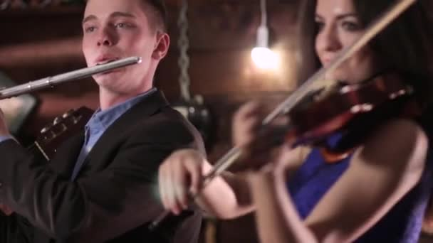 A guy in a jacket and shirt plays the flute, and a beautiful brunette in a blue dress playing the violin. Two people musician reproduce music.