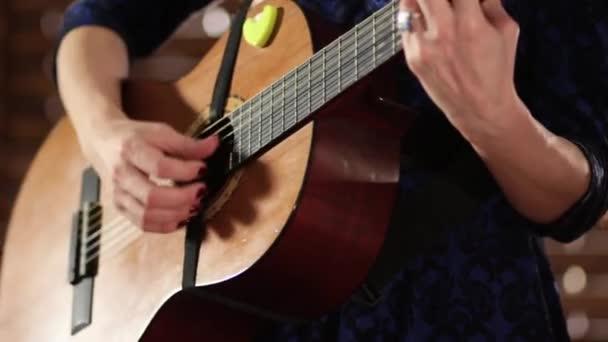 Ruce na struny na akustickou kytaru. Detail. Dívka v modrých šatech dokončí hru na hudební nástroj.