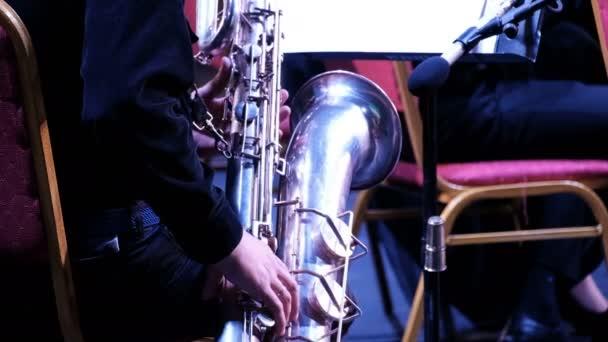 Mužská ruka v černém obleku na velkém saxofonu v jazzové kapele. Detailní záběr. Zadní pohled. Hudebník dechové kapely. Slavnostní koncert symfonického orchestru.