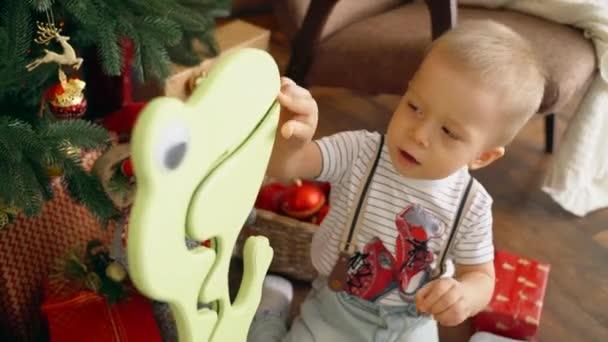 Ein kleiner Junge taucht eine Münze in ein Sparschwein für eiserne Münzen. Sparschwein für Geld in Form eines Dinosauriers.