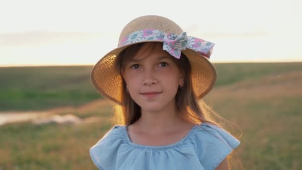 Portrét mladé dívky v klobouku při západu slunce.