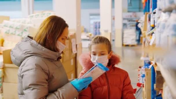 Mutter und Tochter im Großhandelslager wählen die Waren aus. Frau mit Tochter in Arztmasken in einem Geschäft.
